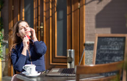 Businesswoman with credit card. And laptop sitting at a table in a cafe on the street Royalty Free Stock Photography
