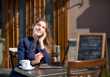 Businesswoman with credit card. And laptop sitting at a table in a cafe on the street Stock Photos