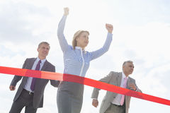 Businesswoman crossing finishing line with colleagues in background Stock Images