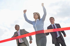Businesswoman crossing finishing line with colleagues in background Stock Image