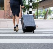 Businesswoman crossing street with luggage Royalty Free Stock Images