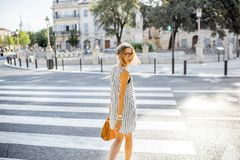 Businesswoman crossing the street. Young stylish business woman crossing the street in the old city in France Royalty Free Stock Images