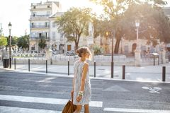 Businesswoman crossing the street. Young stylish business woman crossing the street in the old city in France Royalty Free Stock Image