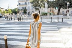 Businesswoman crossing the street. Young stylish business woman crossing the street in the old city in France Stock Photos