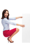 Businesswoman crouching by blank board Royalty Free Stock Image