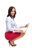 Businesswoman crouching with laptop Royalty Free Stock Photos