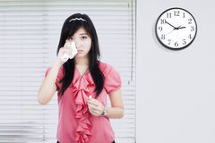 Businesswoman crying with clock on wall Royalty Free Stock Photos
