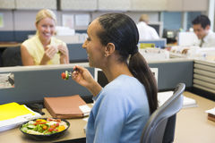 Businesswoman in cubicle eating salad and smiling Royalty Free Stock Photos