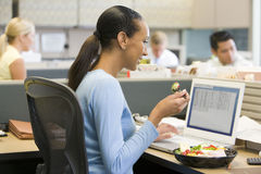 Businesswoman in cubicle eating sushi smiling. Businesswoman in cubicle eating sushi at computer smiling Stock Photo