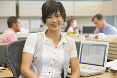 Businesswoman in cubicle smiling Stock Photos