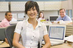 Businesswoman in cubicle smiling. At camera Royalty Free Stock Photo