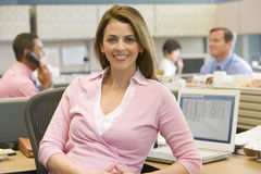 Businesswoman in cubicle smiling. At camera Stock Photos