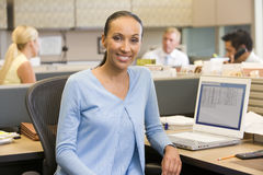 Businesswoman in cubicle smiling. At camera Royalty Free Stock Photography
