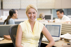 Businesswoman in cubicle smiling. At camera Royalty Free Stock Image