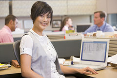 Businesswoman in cubicle smiling. Businesswoman working in office cubicle smiling Stock Images
