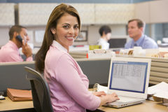 Businesswoman in cubicle smiling. Businesswoman working in office cubicle smiling Stock Photography