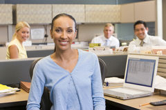 Businesswoman in cubicle smiling Stock Photo