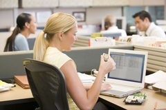 Businesswoman in cubicle using laptop eating sushi Royalty Free Stock Images