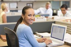 Businesswoman in cubicle using laptop smiling. At camera Stock Photos