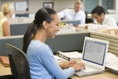 Businesswoman in cubicle using laptop smiling. At camera Royalty Free Stock Photos