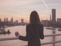 Businesswoman with cup admiring sunrise in London Stock Images