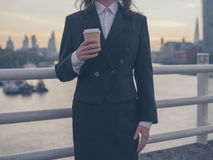 Businesswoman with cup admiring sunrise in London Stock Photo
