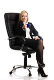 Businesswoman with cup of tea. Attractive blond businesswoman sat in leather chair with cup of tea, white background Royalty Free Stock Photos