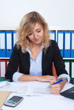 Businesswoman with curly blond hair writing note Royalty Free Stock Photography
