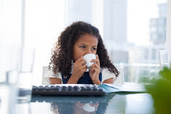 Businesswoman with curly hair looking away while drinking coffee Stock Image