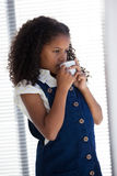 Businesswoman with curly having coffee while standing by window Royalty Free Stock Photos