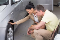 Businesswoman and customer discussing details of car tire Stock Photo