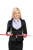Businesswoman cutting a red ribbon Royalty Free Stock Photography