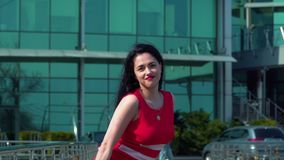 Businesswoman dancing at the background of business center. Beautiful businesswoman is dancing at the background of business center. Stylish brunette feels stock video footage