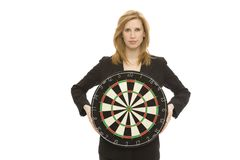 Businesswoman with dart board. Businesswoman in a suit holds a dart board Royalty Free Stock Photo