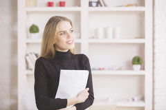 Businesswoman daydreaming in office. Portrait of charming blonde businesswoman with document in hands daydreaming in modern office. White shelves with various Royalty Free Stock Photo