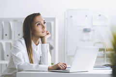 Businesswoman daydreaming in a white office. Portrait of a dreamy woman in a white blouse in her office. She is daydreaming with her hand on a laptop keyboard Royalty Free Stock Photos