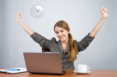 Businesswoman at desk with arms. Thrown up, while looking at camera Royalty Free Stock Photography
