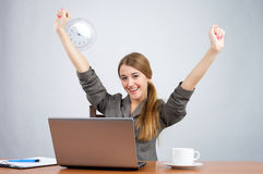 Businesswoman at desk with arms thrown up Stock Image