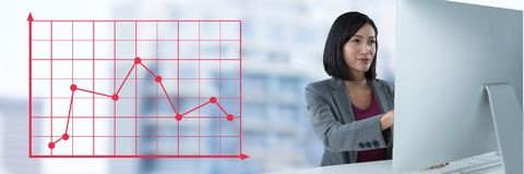 Businesswoman at desk with computer and grid chart points line. Digital composite of Businesswoman at desk with computer and grid chart points line royalty free stock photos