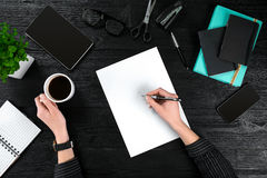 Businesswoman desk with with different objects. A woman`s hand writes in a notebook Stock Photography