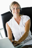 Businesswoman at desk with headset. Facing camera royalty free stock photography