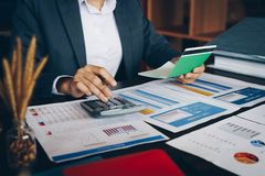 Businesswoman on desk in office using calculator to calculate sa. Ving account passbook and statement with financial report .Female accountant or banker use royalty free stock image