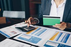 Businesswoman on desk in office using calculator to calculate sa. Ving account passbook and statement with financial report .Female accountant or banker use royalty free stock photography