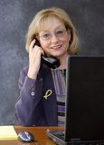 Businesswoman at desk with telephone. And notebook computer, smiling stock images