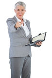 Businesswoman with diary pointing her finger at camera Royalty Free Stock Image
