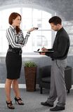 Businesswoman dictating to assistant. Standing in office, assistant taking notes Royalty Free Stock Photo