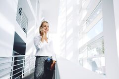 Woman successful lawyer talking on mobile phone after work on digital tablet