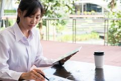 Businesswoman with digital tablet & financial summary graph sitt Royalty Free Stock Photography