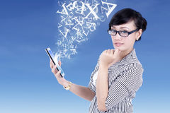 Businesswoman and digital tablet with flying letters Royalty Free Stock Photos
