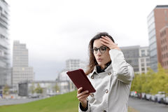 Businesswoman with digital tablet. Reading bad news Royalty Free Stock Photography